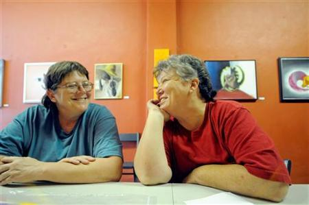 Cheryle Rudd (L) and Kitty Lambert, set to be married as soon as the clock strikes 12:01 on Sunday morning, sit in Lambert's art gallery in Buffalo, New York July 21, 2011. REUTERS/Doug Benz