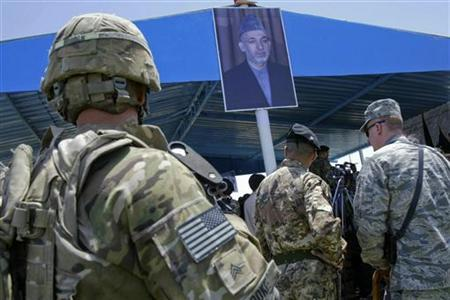 A picture of Afghan President Hamid Karzai hangs in front of a tent during a ceremony to hand over control of security in the city of Herat July 21, 2011. REUTERS/Mohammad Shoib