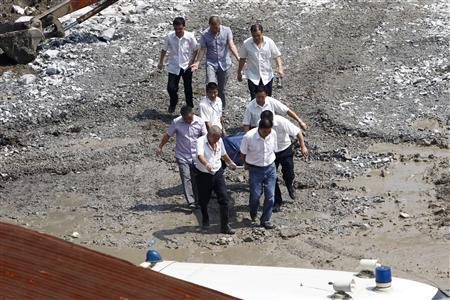 Rescuers carry a body of a victim discovered among the wreckage after two carriages from a bullet train derailed and fell off a bridge in Wenzhou, Zhejiang province July 24, 2011. REUTERS/Aly Song