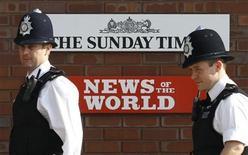 <p>Foto de archivo de unos policías en la entrada de News International en Londres, jul 10 2011. Ministros británicos criticados por sus lazos con News Corp, el imperio de medios de Rupert Murdoch en el centro del escándalo por escuchas telefónicas, eran sometidos a un creciente escrutinio esta semana mientras salen a la luz detalles de sus reuniones con ejecutivos de la compañía. REUTERS/Luke MacGregor</p>
