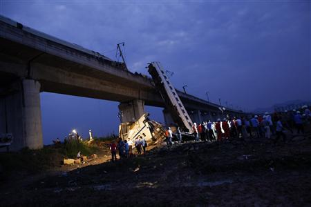 Rescuers carry out rescue operations after two carriages from a bullet train derailed and fell off a bridge in Wenzhou, Zhejiang province July 24, 2011. REUTERS/Aly Song