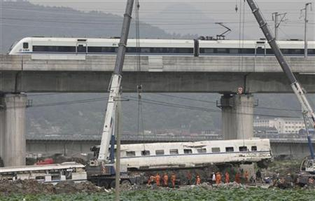 A high speed bullet train runs past a railway bridge as workers use cranes to lift a wrecked carriage (BELOW) onto a truck after two trains crashed and derailed in Wenzhou, Zhejiang province, July 26, 2011. REUTERS/China Daily