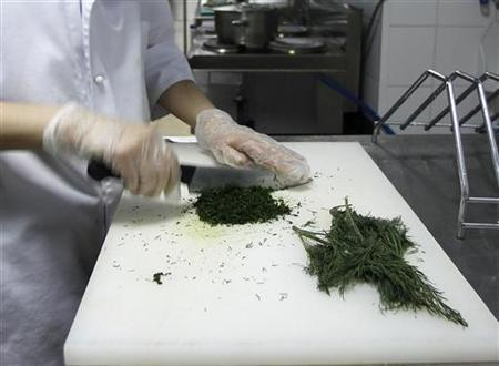 A cook chops dill at a restaurant in Moscow July 20, 2011. REUTERS/Grigory Dukor