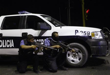 State policemen take cover behind a patrol vehicle during a police operation to regain control of a jail in Ciudad Juarez July 25, 2011. REUTERS/Jose Luis Gonzalez