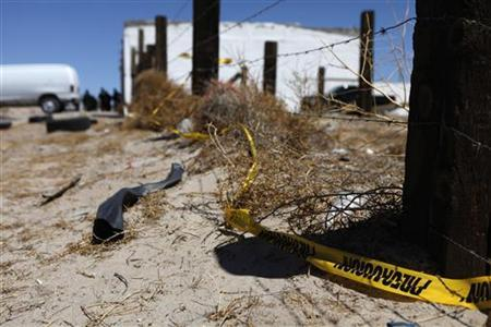 A police cordon is seen at a crime scene where two men were gunned down by unknown assailants on the outskirts of Ciudad Juarez June 10, 2011. REUTERS/Tomas Bravo