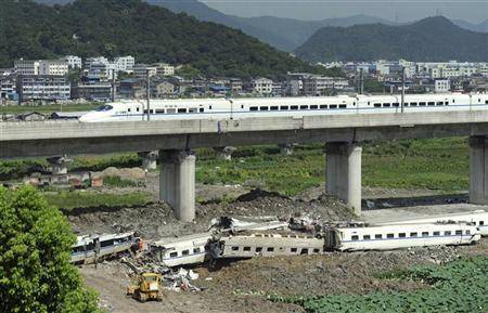 A high speed bullet train runs past a railway bridge past carriage wreckage (below) after two trains crashed and derailed in Wenzhou, Zhejiang province July 25, 2011. REUTERS/China Daily