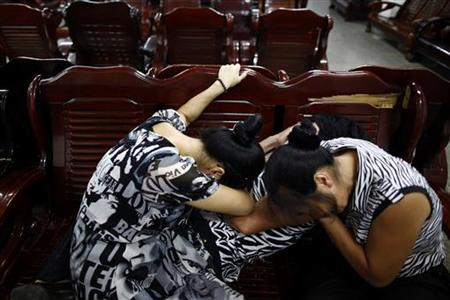 Women cry as relatives console her inside a morgue where people had gathered to search for their missing kin who were passengers on two bullet trains that had crashed in Wenzhou, Zhejiang province, July 25, 2011. REUTERS/Aly Song
