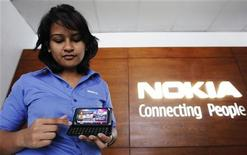 <p>An employee shows a Nokia E7 model phone to a customer at a Nokia show room run by Sri Lankan conglomerate Softlogic in Colombo May 23, 2011. REUTERS/Dinuka Liyanawatte</p>
