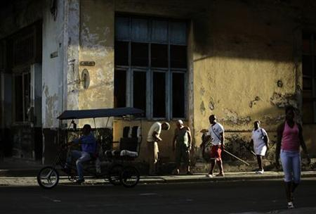 A man looks for customers on his tricycle taxi in Havana July 28, 2011. REUTERS/Desmond Boylan