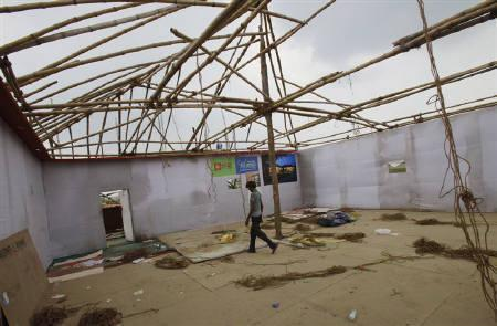 A man walks inside a tent that was formerly used by builders for residential apartments bookings at Greater Noida, India July 26, 2011.  REUTERS/Adnan Abidi