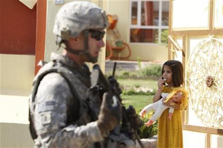 A U.S. soldier attached to the Golden Lions forces walks past a girl carrying her doll, during a patrol in the city of Kirkuk, 250 km (155 miles) north of Baghdad July 20, 2011. REUTERS/Saad Shalash