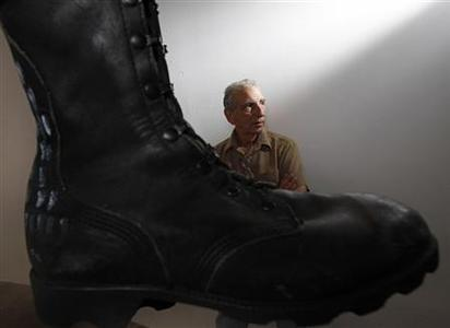 Joe Fornelli, artist liason for the National Veterans Art Museum, is seen beside Jon Turner's ''Prayer Boots'' in Chicago July 20, 2011. REUTERS/Jim Young