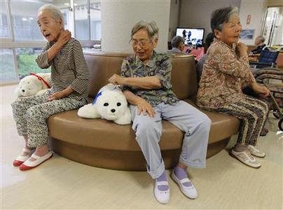Ayako Shizo (C) aged 85, taps a therapeutic robot named Paro as she sits with other residents at the Suisyoen retirement home about 30 km (19 miles) south of the tsunami-crippled nuclear plant in Iwaki, Fukushima prefecture, July 28, 2011. REUTERS/Kim Kyung-Hoon