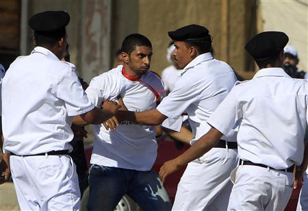 A supporter of Egypt's former president Hosni Mubarak is stopped by police officers during clashes with anti-Mubarak protesters outside the police academy where his trial will take place, in Cairo August 3, 2011. REUTERS/Amr Abdallah Dalsh