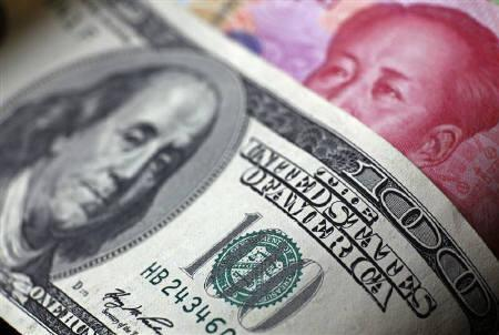 A Chinese 100 yuan banknote is placed under a $100 banknote (top) in this photo illustration taken in Beijing in this November 7, 2010 file photo. REUTERS/Petar Kujundzic/Files