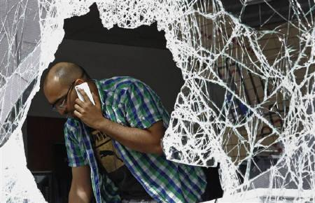 A man looks out of the broken window of a mobile telephone shop that was looted overnight at the Tottenham Hale Retail Park in Tottenham, north London August 7, 2011. REUTERS/Luke MacGregor