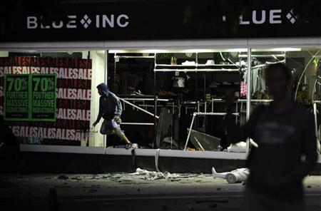 A looter jumps out from a smashed-up department store in Peckham, south London August 8, 2011. REUTERS/Dylan Martinez