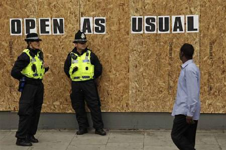 Police officers from Wales patrol outside a boarded up shop in Streatham, south London August 10, 2011. REUTERS/Stefan Wermuth