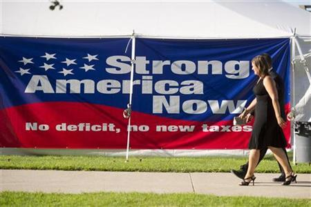 Guests walk past a banner as they arrive for a Republican Presidential Debate in Ames, Iowa, August 11, 2011. REUTERS/Daniel Acker