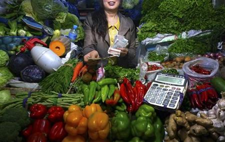 A fruit and vegetable stall owner uses a calculator to work out prices for a customer at a small market in central Beijing, July 7, 2011. REUTERS/David Gray
