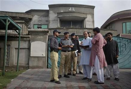 Police and security officials gather outside the residence of an American citizen, whom the U.S. embassy declined to identify, after he was kidnapped in Lahore August 13, 2011. REUTERS/Mohsin Raza