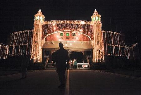 A man is silhouetted against the illuminated Wagah border crossing, along the Pakistan-India border, on August 13, 2011 in celebration of Pakistan's Independence Day. REUTERS/Mohsin Raza