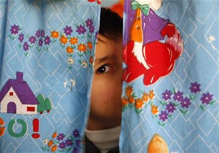 An autistic child peers from between curtains at the Consulting Centre for Autism in Amman, Jordan March 30, 2010. REUTERS/Ali Jarekji