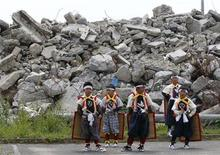 <p>Child performers stand in front of tsunami debris as they prepare for a sword dance to mourn the victims of March 11's earthquake and tsunami at a devastated building in Ofunato, north of Japan, August 14, 2011, during Japan's annual Buddhist ceremony Obon that welcomes back the spirits of the dead. REUTERS/Kim Kyung-Hoon</p>