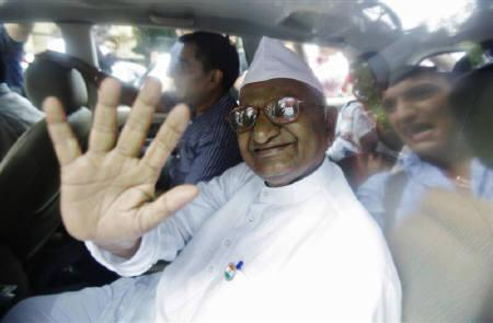 Veteran social activist Anna Hazare waves from a car after being detained by police in New Delhi August 16, 2011. REUTERS/Adnan Abidi