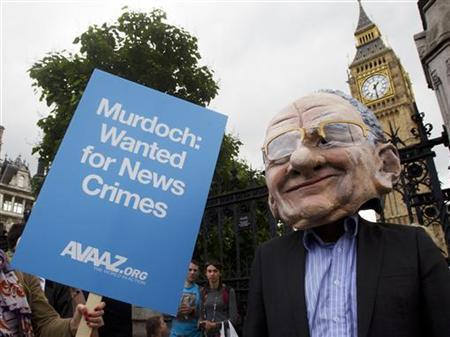 A man wearing a mask depicting News Corp Chief Executive and Chairman Rupert Murdoch protests during a parliamentary committee on phone hacking at Portcullis House in London July 19, 2011. REUTERS/Olivia Harris