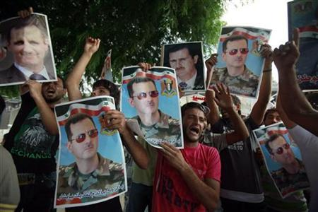 Syrians living in Lebanon, chant slogans in support of Syria's President Bashar al-Assad and carry pictures of him, as an anti-government protest takes place at the same time a few metres away near the government palace in Beirut August 15, 2011. REUTERS/ Sharif Karim