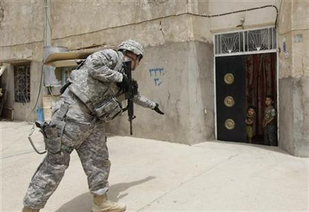 A U.S. soldier throws sweets to children during a patrol in the city of Kirkuk, 250 km (155 miles) north of Baghdad July 20, 2011. REUTERS/Saad Shalash