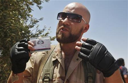 Irish-Libyan rebel fighter Husam Najjair speaks to reporters at a front line checkpoint near Tiji in western Libya, August 1, 2011. REUTERS/Bob Strong