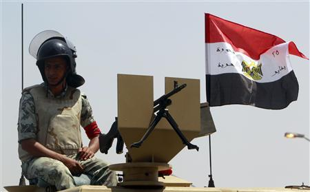An Egyptian army soldier sits beside an Egyptian flag that reads ''Egypt's Revolution of freedom, the 25th of January'' on his vehicle parked near the Israeli embassy as protesters shout slogans against Israel during a protest in front of the Israeli embassy in Cairo August 21, 2011. REUTERS/Amr Abdallah Dalsh