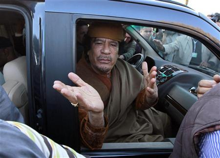 Libya's leader Muammar Gaddafi waves from a car in the compound of Bab Al Azizia in Tripoli, after a meeting with a delegation of five African leaders seeking to mediate in Libya's conflict, in this April 10, 2011 file photo. REUTERS/Louafi Larbi/Files