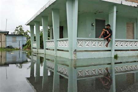 A man sits outside his home after Hurricane Irene hit the municipality of Loiza, at the north east side of the Caribbean Island, in Loiza August 22, 2011. REUTERS/Ana Martinez