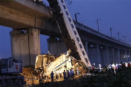 Rescuers carry out rescue operations after two carriages from a bullet train derailed and fell off a bridge in Wenzhou, Zhejiang province, July 24, 2011. REUTERS/Aly Song