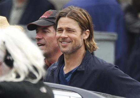 Actor Brad Pitt smiles during the filming of zombie movie 'World War Z' in Glasgow, Scotland August 24, 2011. REUTERS/David Moir
