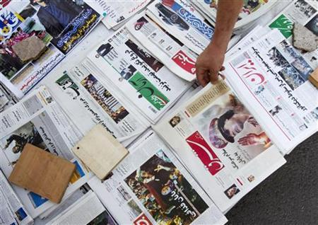 Newspaper front pages showing pictures of Muammar Gaddafi and the events in Libya are seen at a news stand in Tehran August 23, 2011. REUTERS/Morteza Nikoubazl