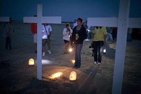 Participants gather around crosses honoring the workers who died on the Deepwater Horizon oil platform, during a service marking the one-year anniversary of the BP Oil Spill in Grand Isle, Louisiana April 20, 2011. REUTERS/Lee Celano