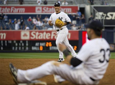New York Yankees second baseman Jorge Posada grins after he nearly pulled first baseman Nick Swisher (33) off the first base bag as he threw out Oakland Athletics batter Anthony Recker for the final out of their 22-9 victory in their MLB American League baseball game at Yankee Stadium in New York, August 25, 2011. REUTERS/Ray Stubblebine