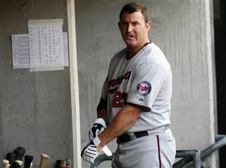 Minnesota Twins' Jim Thome puts on his batting gloves in the dug-out during the first inning of their MLB American League baseball game against the Detroit Tigers in Detroit, Michigan August 15, 2011. REUTERS/Rebecca Cook