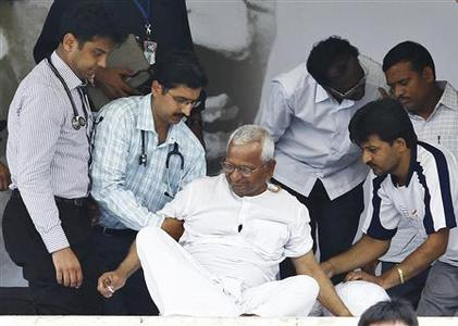 Veteran Indian social activist Anna Hazare (C) is assisted by doctors to stand up on the 12th day of his fast at Ramlila grounds in New Delhi August 27, 2011. REUTERS/Adnan Abidi