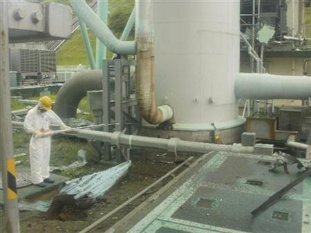 Tokyo Electric Power Co (TEPCO)'s handout shows a worker in protective gear measuring radiation levels at the bottom of a ventilation stack standing between Fukushima Daiichi nuclear power plant's No.1 and No.2 reactors, where radiation exceeding 10 sieverts (10,000 millisieverts) per hour was found, in Fukushima prefecture, northern Japan August 1, 2011, released by TEPCO August 2, 2011. REUTERS/Tokyo Electric Power Co/Handout