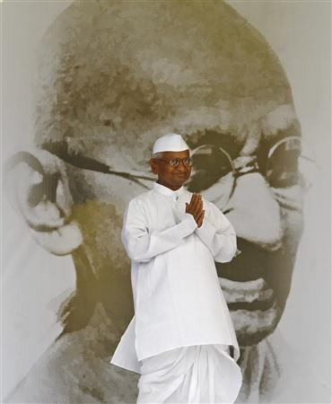 Veteran Indian social activist Anna Hazare gestures to his supporters in front of a portrait of Mahatma Gandhi on the 12th day of his fast at Ramlila grounds in New Delhi August 27, 2011. REUTERS/Adnan Abidi