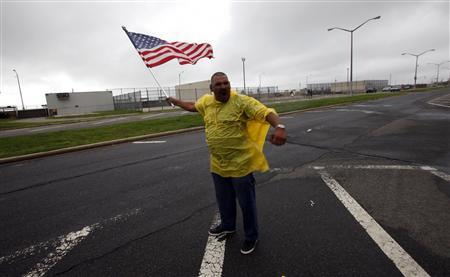 Jimmy Romero holds an American flag as he stands in the rain and wind along Rockaway Beach in New York City August 27, 2011, ahead of Hurricane Irene. REUTERS/Mike Segar