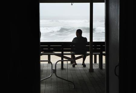 A man sits on a bench to watch waves pushed onto Long Island by the winds of Hurricane Irene in East Hampton Village, New York August 27, 2011. REUTERS/Lucas Jackson