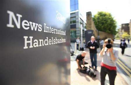 Camera crews and photographers wait outside News International's headquarters in east London, July 11, 2011. REUTERS/Andrew Winning