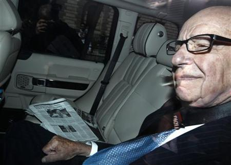 News Corp Chief Executive and Chairman Rupert Murdoch arrives, sitting next to a copy of the Wall Street Journal, to attend a parliamentary committee hearing at Portcullis House in London July 19, 2011. REUTERS/Andrew Winning