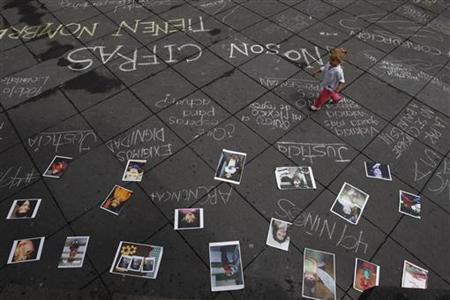 A girl walks near graffiti and photographs of victims of drug violence and victims of a fire incident at a day-care centre during a protest in Guadalajara August 28, 2011. REUTERS/Alejandro Acosta